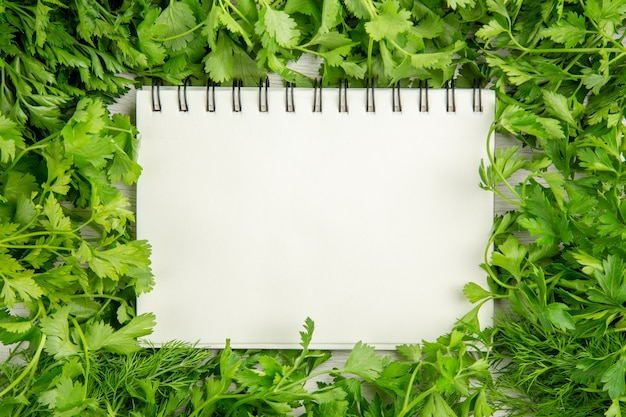 Top view fresh greens with notepad on white background