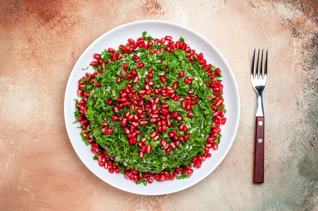 Vista dall'alto verdure fresche con melograni sbucciati sul tavolo chiaro di colore verde della frutta
