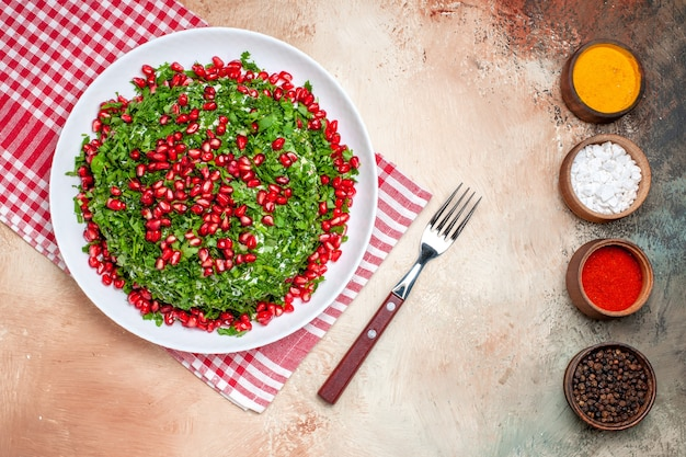 Top view fresh greens with peeled pomegranates on light table fruit greens meal