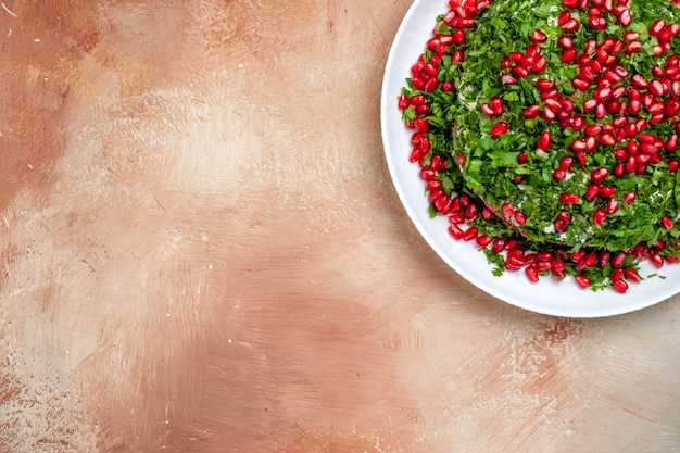 Top view fresh greens with peeled pomegranates on light table fruits green color