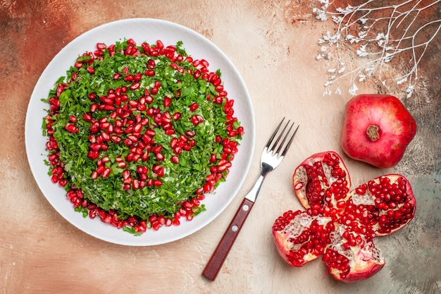 Top view fresh greens with peeled pomegranates on light table green fruit meal