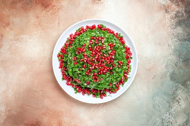 ライトテーブルのフルーツグリーン色に皮をむいたザクロとトップビューの新鮮な緑