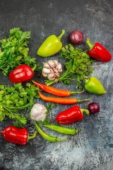 Vista dall'alto verdure fresche con peperoni e aglio su tavolo grigio chiaro insalata pasto foto colore piatto cibo vita sana