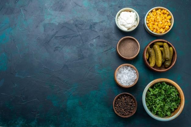 紺色の机の上にピクルスと調味料を添えた新鮮な野菜の上面図。