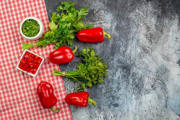 ライトグレーのテーブルに赤いピーマンとトップビューの新鮮な緑