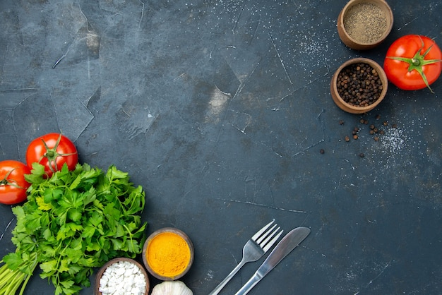 어두운 탁자에 토마토와 조미료를 넣은 신선한 채소