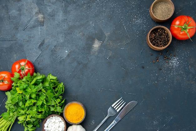 Vista dall'alto verdure fresche con pomodori e condimenti sul tavolo scuro