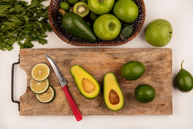 Top view of fresh half avocado with knife on a wooden kitchen board with limes with apples and kiwi on a bucket on a white background