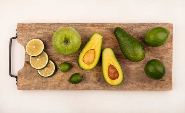 Top view of fresh half avocado on a wooden kitchen board with limes and feijoas on a white wall