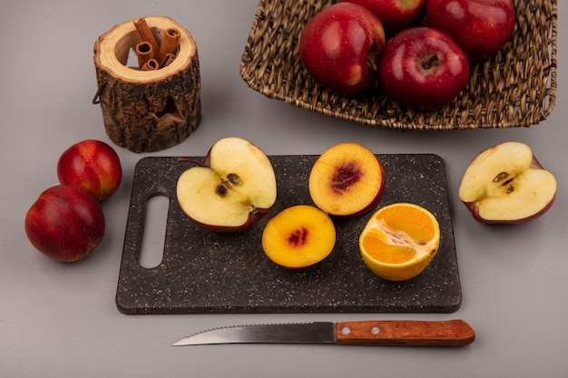Top view of fresh half peaches on a black kitchen board with tangerine and apple with knife with red apples on a wicker tray on a grey background