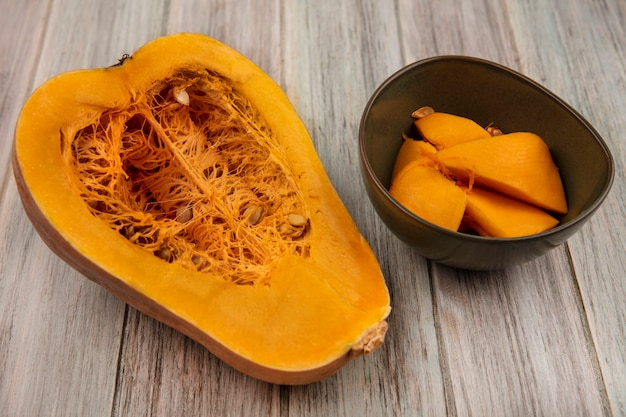 Top view of fresh half pumpkin with its seeds with pumpkin slices on a bowl on a grey wooden wall