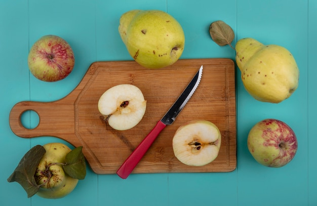 Vista dall'alto di mele fresche dimezzate su una tavola di cucina in legno con coltello con mele cotogne isolato su uno sfondo blu