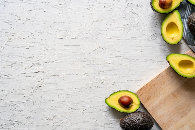 Top view of fresh halved avocados and a wooden cutting board on a white surface, copy space