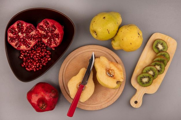 Vista dall'alto di mele cotogne fresche dimezzate su una tavola da cucina in legno con melograni su una ciotola con fette di kiwi su una tavola da cucina in legno