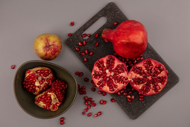 Top view of fresh halved and whole pomegranates on a black kitchen board with open pomegranates on a bowl