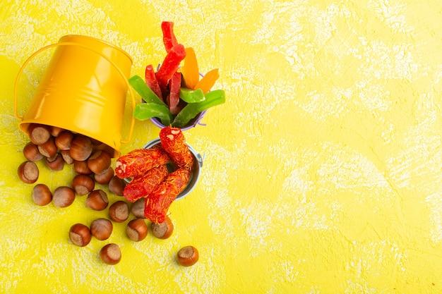 Vista dall'alto di nocciole fresche insieme a torrone e marmellate sulla superficie gialla