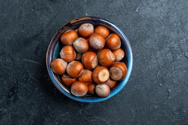 暗い表面の小さな鍋の中の新鮮なヘーゼルナッツの上面図ナッツヘーゼルナッツクルミスナックピーナッツ