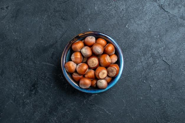 暗い背景の小さな鍋の中の新鮮なヘーゼルナッツの上面図ナッツヘーゼルナッツクルミスナックピーナッツ