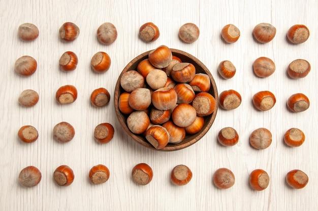 Nocciole fresche vista dall'alto su arachidi dado da scrivania bianca