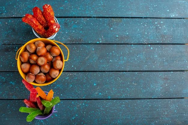 Vista dall'alto di nocciole fresche con torrone e marmellate sulla superficie blu