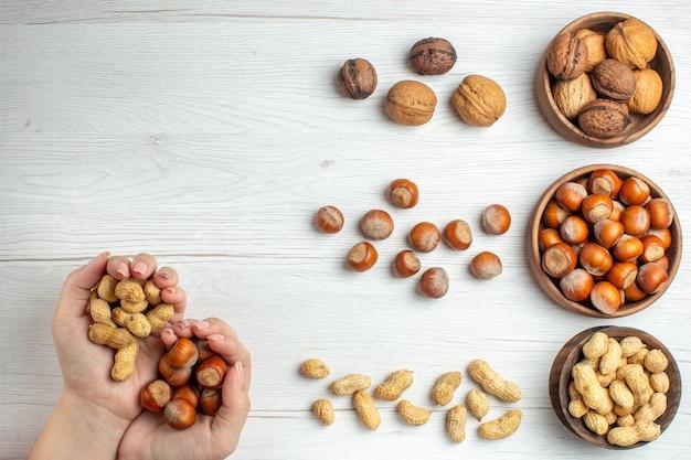 Vista dall'alto nocciole fresche con arachidi e noci sul tavolo bianco