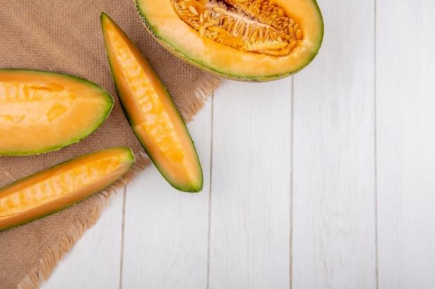 Vista dall'alto di melone cantalupo fresco e sano con fette di tela di sacco su bianco