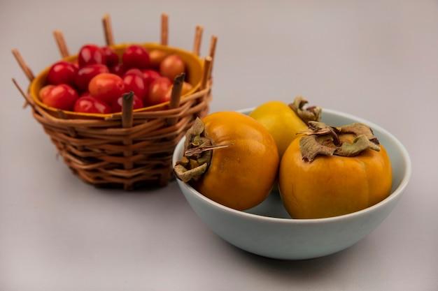 Vista dall'alto di frutti di corniola freschi e sani su un secchio con frutti di cachi su una ciotola su uno sfondo grigio