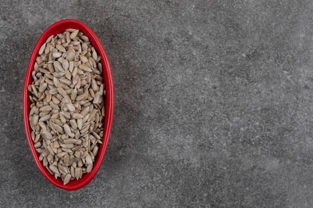 Vista dall'alto della ciotola rossa della locanda di semi di girasole sani freschi