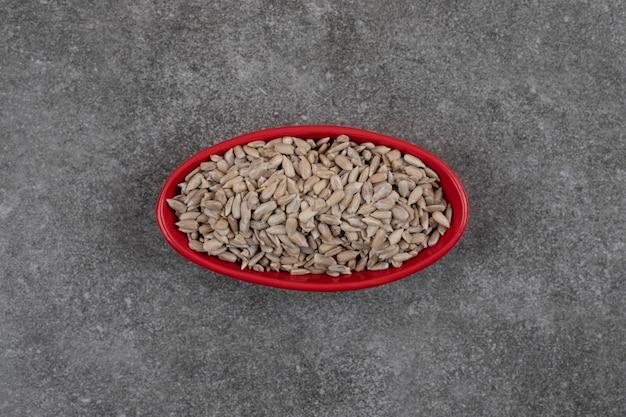 Vista dall'alto di semi di girasole sani freschi in una ciotola rossa.