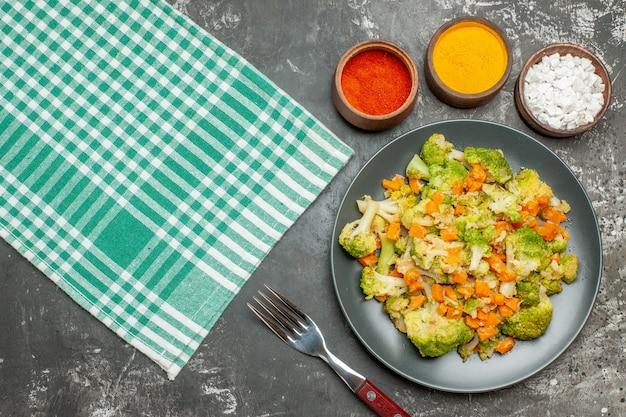 Vista dall'alto di insalata di verdure fresca e sana sul tovagliolo spogliato verde sul tavolo grigio