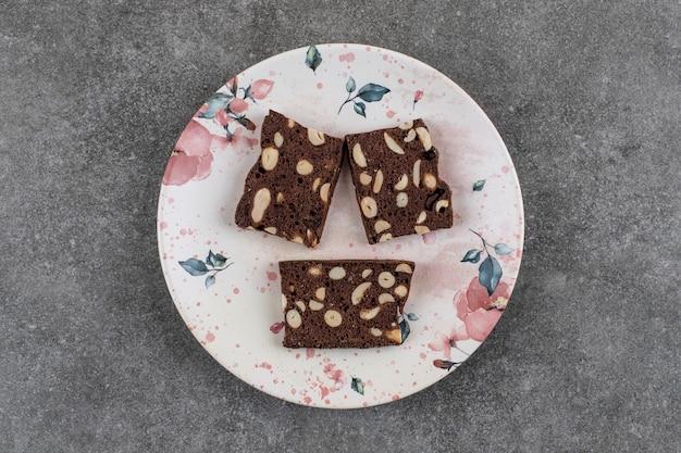 Vista dall'alto di fette di torta fresca fatta in casa sul piatto su superficie grigia