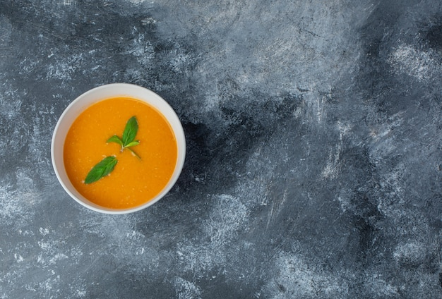 Vista dall'alto della zuppa fresca fatta in casa in una ciotola bianca sul tavolo grigio