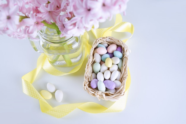 Top view of fresh hyacinth flower in vase with easter eggs candies in basket on white