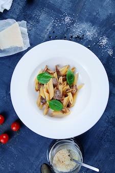 トップビューキノコ、バジル、子牛のフレッシュイタリアンパスタペンネ。自家製料理のコンセプトです。イタリア料理。