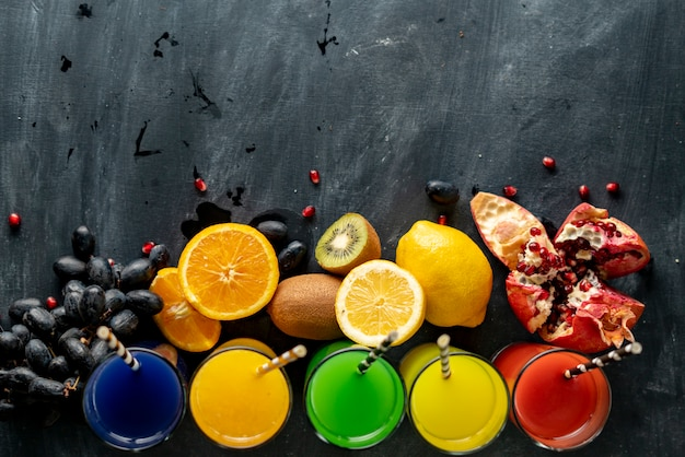 Top view of fresh juice variety, different fruits around, copy space for your text on a black tables