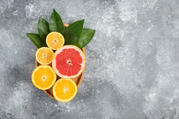 Vista dall'alto di fette di frutta fresca e succosa con foglie su piatto di legno.