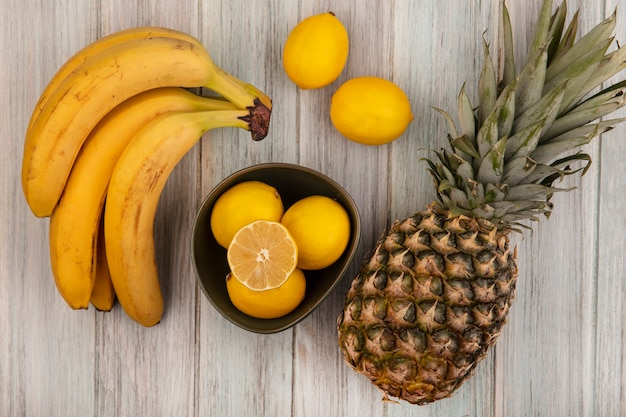 Top view of fresh and juicy lemons on a bowl with pineapple bananas and lemons isolated on a grey wooden surface