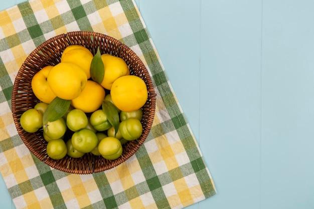 Vista dall'alto di pesche fresche e succose su un secchio con prugne ciliegia verdi su una tovaglia a quadri su sfondo blu con spazio di copia