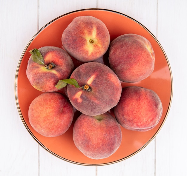 Top view of fresh and juicy peaches onn orange plate on white