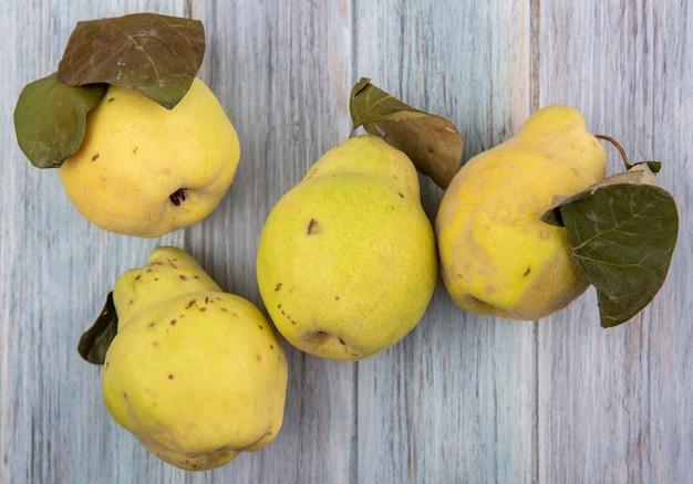 Vista dall'alto di frutta mela cotogna fresca e succosa con foglie su un fondo di legno grigio