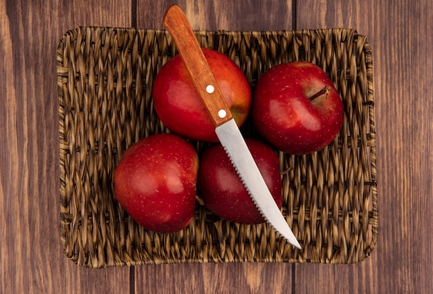 Top view of fresh juicy and red apples on a wicker tray with knife on a wooden background