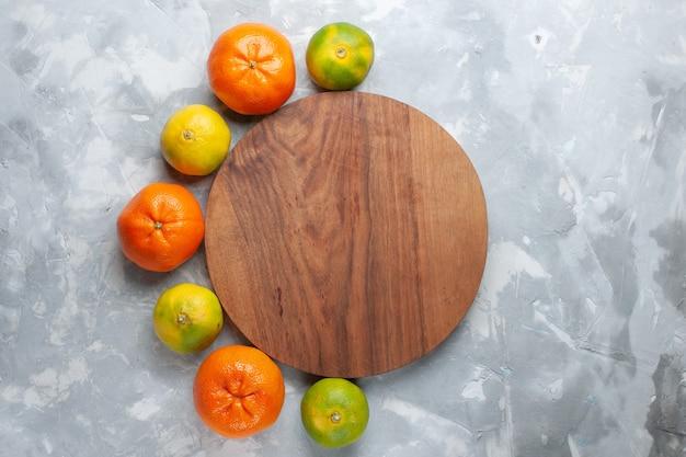 Vista superiore mandarini succosi freschi agrumi morbidi sulla scrivania bianco-chiaro agrumi esotici tropicali