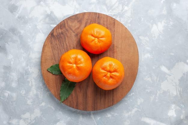 トップビュー新鮮なジューシーなみかんまろやかな柑橘類オレンジ色の白い机に柑橘系の果物エキゾチックな熱帯