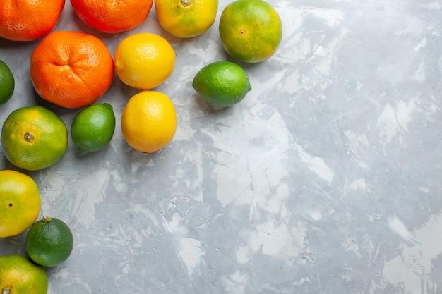 トップビュー新鮮なジューシーなみかんまろやかな柑橘類オレンジ色の白い机の上にレモンで着色柑橘系の果物エキゾチックな熱帯