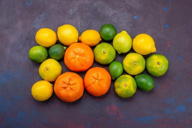 暗い机の上に他の柑橘類で着色されたオレンジ色の新鮮なジューシーなみかんの上面図柑橘類の熱帯のエキゾチックなオレンジ色の果実