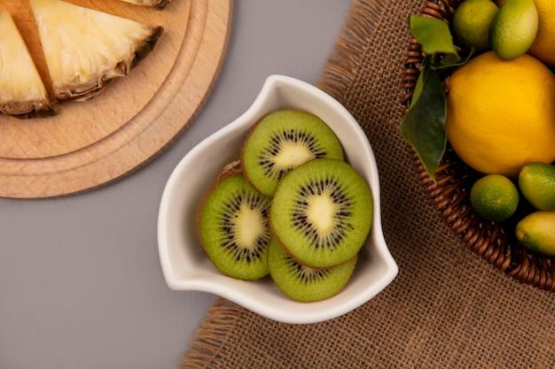 Vista dall'alto di fette di kiwi freschi su una ciotola con frutta come kinkan e limoni su un secchio su un panno di sacco su una superficie grigia