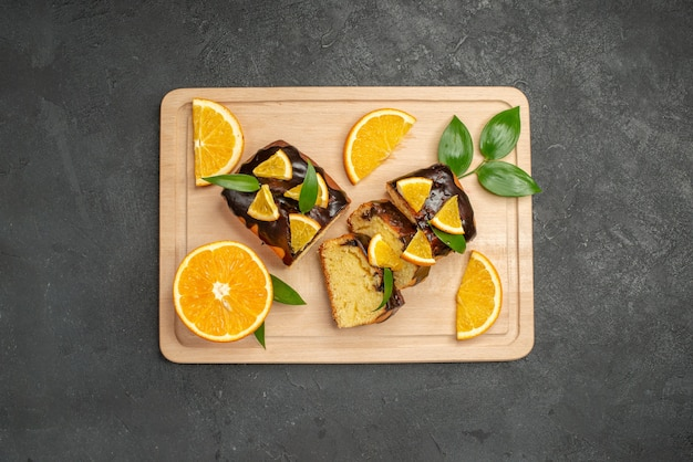 Top view of fresh lemon slices and chopped cake slices on dark background