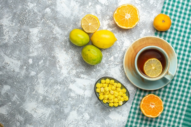Вид сверху свежие дольки лимона с чашкой чая на светлом столе
