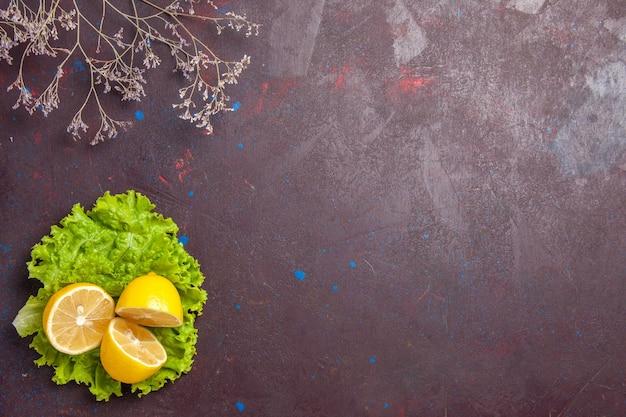 Vista dall'alto di fette di limone fresco con insalata verde al buio