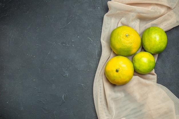 Vista dall'alto limoni freschi beige scialle tule su superficie scura con copia spazio
